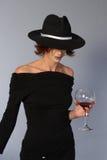 Frau mit schwarzem Kleid- und Wein- und Mafiahut Lizenzfreies Stockbild