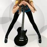 Frau mit schwarzer elektrischer Gitarre Stockfotografie