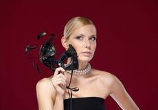 Frau mit schwarzer Maskeradeschablone mit Federn Stockbilder