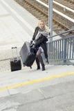 Frau mit schweren Koffern gehend herauf Treppe an der Bahnstation Lizenzfreie Stockbilder