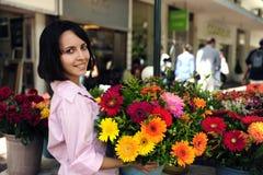 Frau mit sehr großem Blumenstrauß der Blumen draußen stockbild