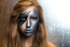Frau mit silbernem Teil des Gesichtes stockfoto
