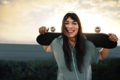 Frau mit Skateboard draußen Stockbild