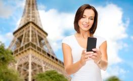 Frau mit Smartphone über Eiffelturm Lizenzfreie Stockfotografie