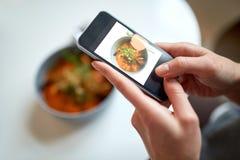 Frau mit Smartphone Lebensmittel am Café fotografierend Stockbilder