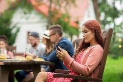 Frau mit Smartphone und Freunden am Sommerfest Stockfoto