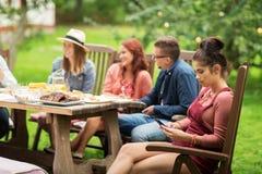 Frau mit Smartphone und Freunden am Sommerfest Stockfotografie