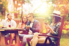 Frau mit Smartphone und Freunden am Sommerfest Stockbilder