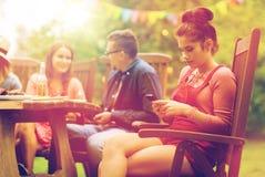 Frau mit Smartphone und Freunden am Sommerfest Stockbild