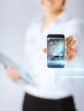 Frau mit Smartphone und virtuellen Schirmen Stockbild