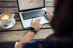 Frau mit smartwatch unter Verwendung des Laptops am Café Stockfoto