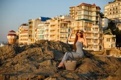 Frau mit Sommerstrandkleid an sitzt auf einem Felsen und genießt Sonne im Urlaub Attraktives schönes Mädchen mit weißem Stroh Stockfotos