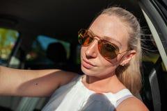 Frau mit Sonnenbrille in einem Auto Lizenzfreie Stockfotografie