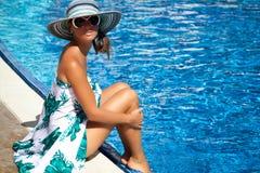 Frau mit Sonnenbrille entspannen sich an der Luxuspoolseite Stockfotos