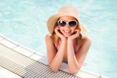 Frau mit Sonnenbrille und Hut im Swimmingpool, Wasser Lizenzfreies Stockfoto