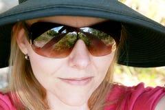 Frau mit Sonnenbrillen und einem Hut Stockfotografie