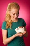 Frau mit Sparschwein in den Händen regte zum Safe auf, Spareinlagen zu speichern Stockfotografie