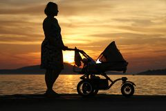 Frau mit Spaziergänger am Sonnenuntergang lizenzfreies stockbild