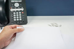 Frau mit Spott herauf Papierblatt- und Büroklammerbefestigung Lizenzfreies Stockfoto