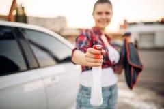 Frau mit Spray in der Hand, Selbstbedienungswaschanlage lizenzfreie stockbilder