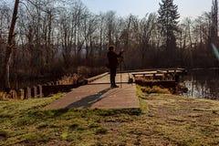 Frau mit Stativ und Kamera lizenzfreies stockbild