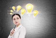 Frau mit Stift und vielen Glühlampen Lizenzfreies Stockfoto