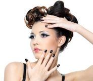 Frau mit stilvoller Frisur und schwarzen Nägeln Stockfotografie