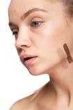 Frau mit Streifen der unterschiedlichen Art der Creme auf Gesicht Lizenzfreies Stockbild