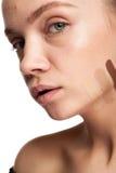 Frau mit Streifen der unterschiedlichen Art der Creme auf Gesicht Stockfotos