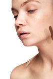 Frau mit Streifen der unterschiedlichen Art der Creme auf Gesicht Lizenzfreies Stockfoto