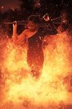 Frau mit Sturmgewehr auf Feuer Stockbild