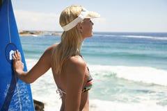 Frau mit Surfbrett am Strand Stockfotografie