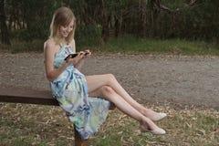 Frau mit Tablette auf Bank Stockfoto