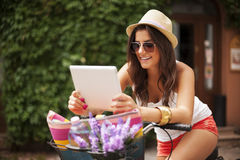 Frau mit Tablette auf Fahrrad Stockbilder