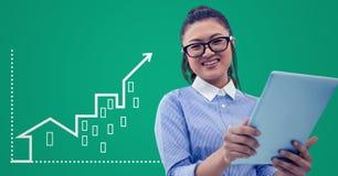 Frau mit Tablette gegen grünen Hintergrund mit weißer Hausgraphik Lizenzfreie Stockfotografie