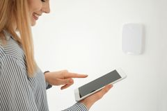 Frau mit Tablette nahe Sicherheitssystem zuhause stockbild