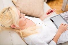 Frau mit Tablette und Kirsche auf dem Sofa Lizenzfreie Stockfotografie