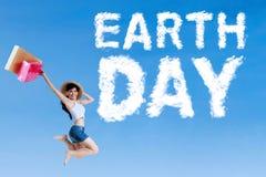 Frau mit Tag der Erde-Text auf Himmel Stockfotografie