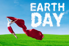 Frau mit Tag der Erde-Text springt am Feld Lizenzfreie Stockfotos