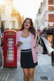 Frau mit Taschen in ihrer Hand kauft auf einem beschäftigten Einkaufen-highstreet in London Lizenzfreies Stockfoto