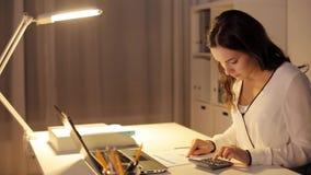 Frau mit Taschenrechner und Papieren im Nachtbüro stock video