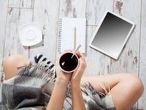 Frau mit Tasse Kaffee, Notizblock und Tablette Stockbild