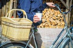 Frau mit Tasse Kaffee und Fahrrad Lizenzfreie Stockfotografie