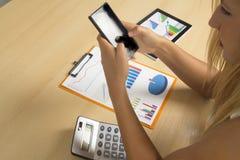 Frau mit Telefon im Büro lizenzfreies stockfoto