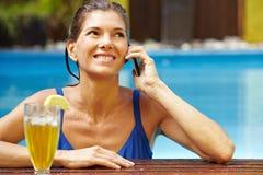 Frau mit Telefon im Pool stockfotos
