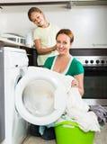 Frau mit Tochter nahe Waschmaschine Lizenzfreies Stockfoto