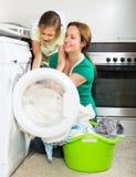 Frau mit Tochter nahe Waschmaschine Stockbilder