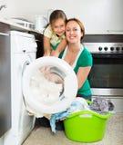 Frau mit Tochter nahe Waschmaschine Lizenzfreies Stockbild