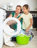 Frau mit Tochter nahe Waschmaschine Stockfoto