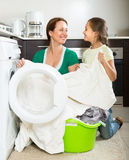 Frau mit Tochter nahe Waschmaschine Stockbild